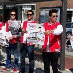 Jongeren houden Ready4Work poster voor zich bij een bushalte.